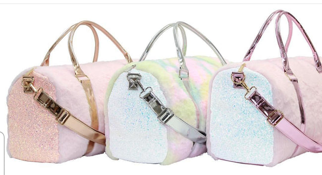 "The Faux Fur Travel Duffel Bag has an adjustable detachable over the shoulder strap.The Faux Fur is Super, with Iridescent and Glitter. Inside is lined pink with a zipped pocket. Hand Carry Iridescent Loop Handles. Perfect for sleepovers, dancers, gymnasts, cheerleading comps and weekend getaways!  Jr Fur Travel Bags come in 2 Beautiful Styles: Pink Faux Fur & Pink Iridescent and white Glitter Pink Faux Fur & Rose Gold Iridescent and Rose Gold Glitter Approximate Outside Dimensions: 18"" X 8.5"" X 9.5"" (L x W"