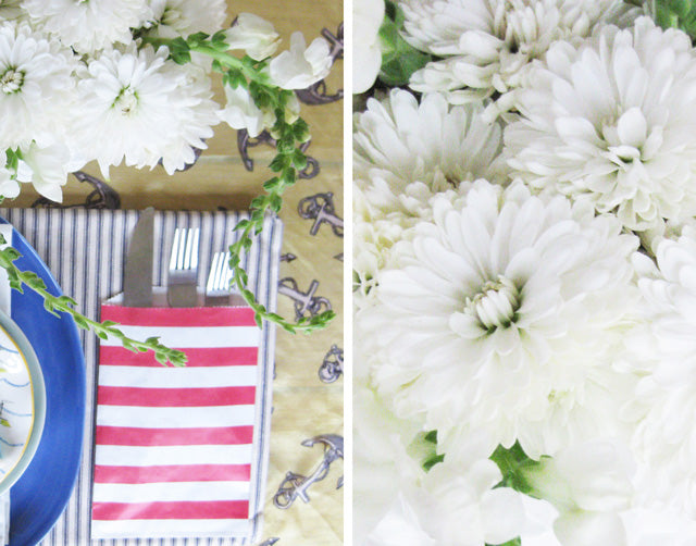 white carnations and cutlery in a red and white striped pocket