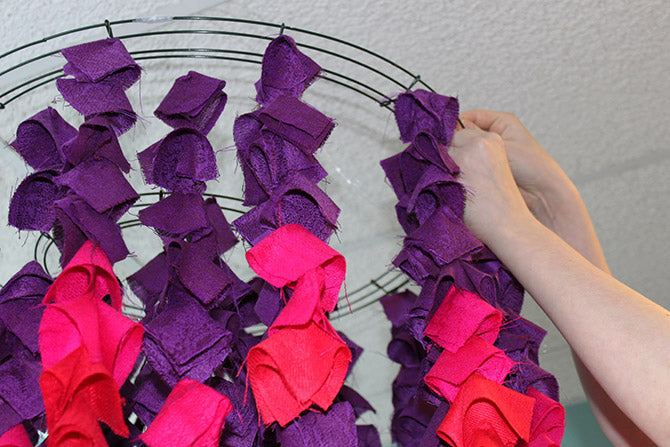 attaching the strands of folded scarve squares on wreath frames for the Ombre Scarf Chandelier