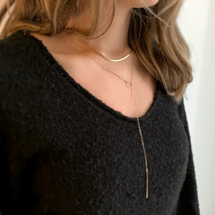 model wearing gold drop bar lariat necklace layered with the gold herringbone necklace