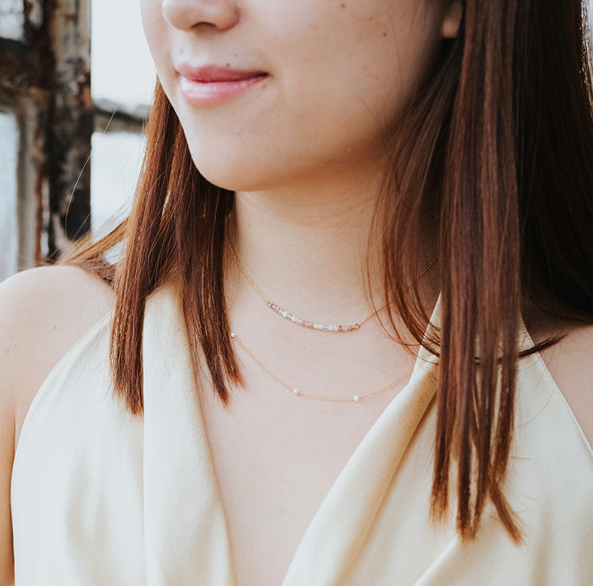 model wearing gold freshwater pearl strand layered with the goddess necklace
