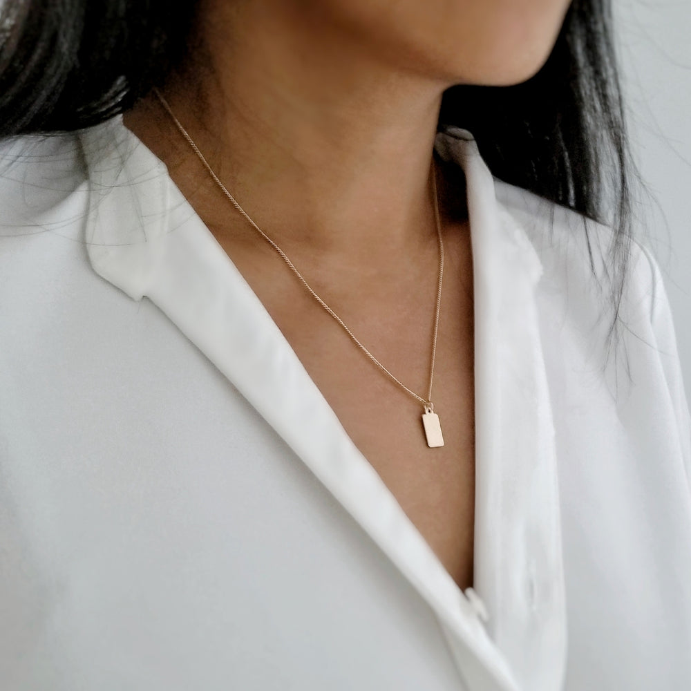 customer wearing gold tag necklace layered with the gold linked necklace