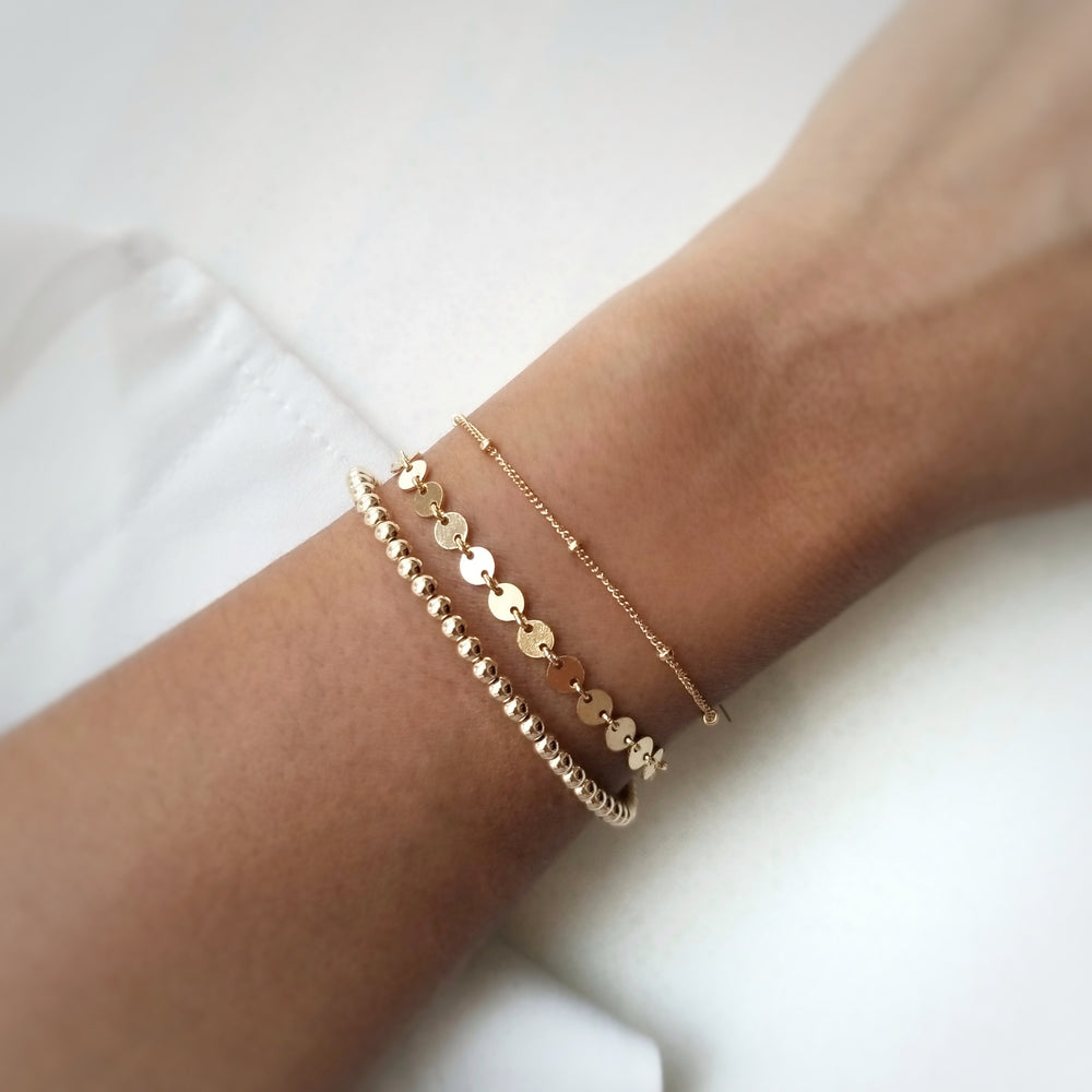 gold filled coin bracelet layered with satellite chain bracelet and gold beaded bracelet