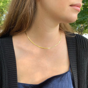 A model wearing the gold herringbone necklace