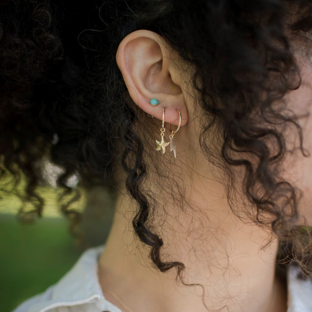 tiny gold hoops with lightning and starfish charm and turquoise stud earrings