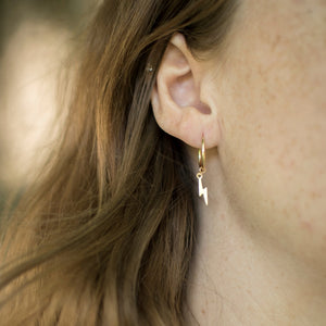 model wearing tiny gold filled hoops with gold lightning bolt charm