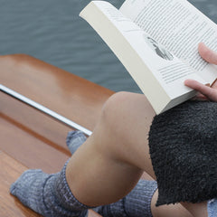 Reading a boat on the boat with Pretty Fly socks on