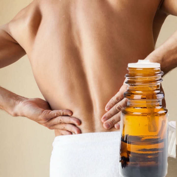 Bare back of a man in a towel, holding his back as if in pain with a bottle of essential oils next to him.