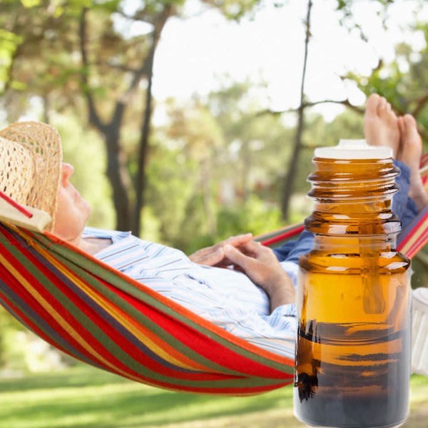 Man laying in a hammock on a sunny day with a bottle of essential oil next to him.  Peaceful and relaxed.