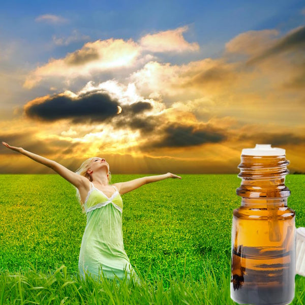 Woman in a field with her arms raise to the sky. There are storm clouds passing by but the sun is coming out to shine on her.  A bottle of essential oil is in the corner.