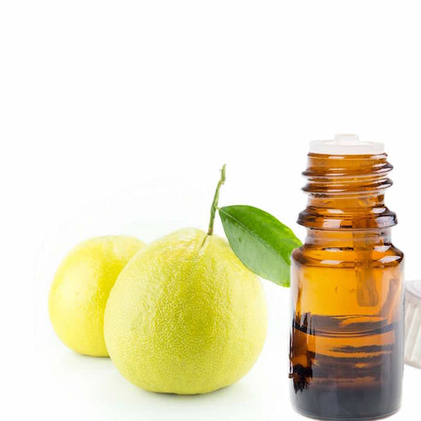 Bergamot fruit next to an open bottle of essential oil.