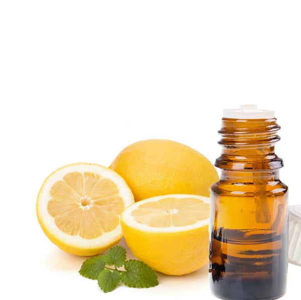 Cut and whole lemon next to a bottle of essential oil
