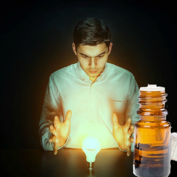Young man staring down at a light bulb with hands up in a pose of awareness. A bottle of essential oil next to him.