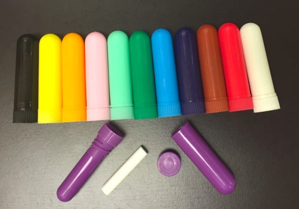 Plastic nasal inhalers for aromatherapy, in various colors, lined in a row.