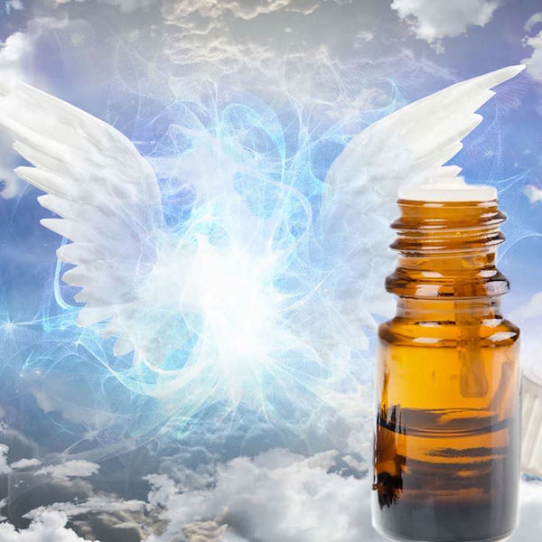 Glowing angel wings in the sky, next to a bottle of essential oils