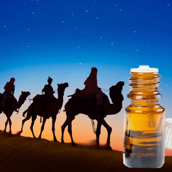 Three Wise Men on camels going through the desert. A bottle of essential oil in the corner.