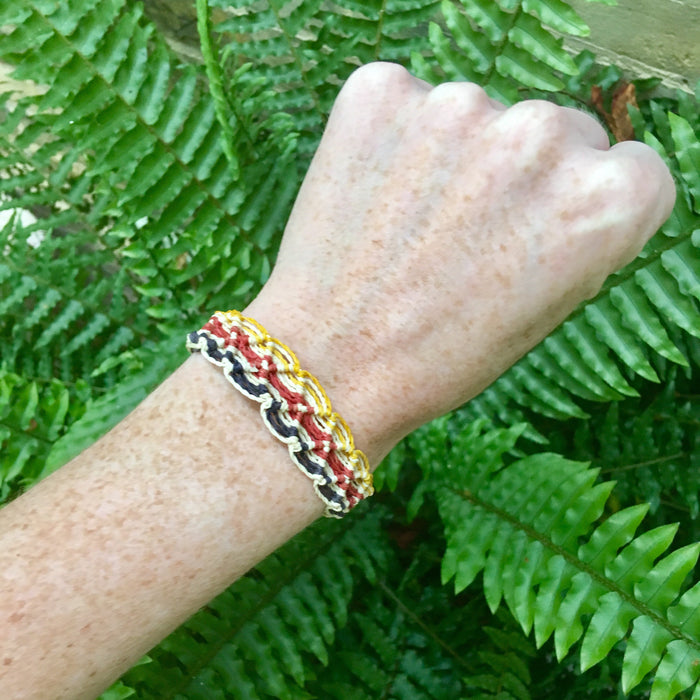 Yellow, black and red string bracelet