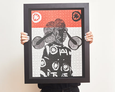 Person holding framed BerlinMagalog artwork puzzle.