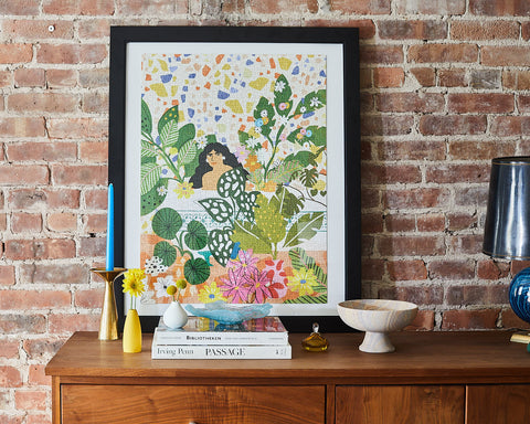 Framed Bathing with Flowers puzzle against brick wall.