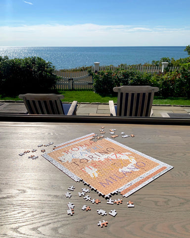 Andiamo art puzzle by Meagan Maguire on wood table overlooking the ocean.