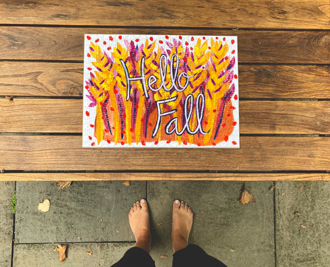 Person's feet as they look down at Hello Fall art puzzle by Mel Reese on wood floor.