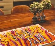 Hello Fall art puzzle by Mel Reese on wood table with plants.
