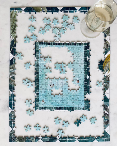 Half-completed Swim Club puzzle on marble table with glass of wine.