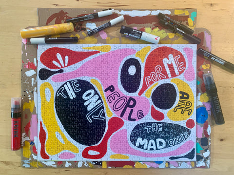 The Mad Ones art puzzle by Marika Wagle on wood table with paint supplies.