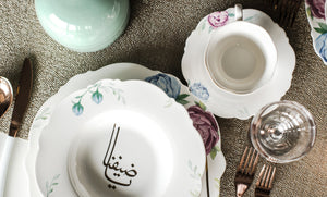 This Flower Calligraphy Dinnerware makes a fashionable, dramatic statement on any tabletop. These fine china pieces feature a luxurious golden thuluth script with some flowers design. The fresh pattern is enhanced by the clean creamy color base.