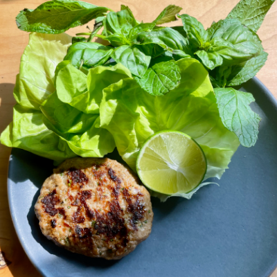 grilled sausage patty on a dark gray plate next to a bouquet of lettuce, fresh herbs and half a lime.