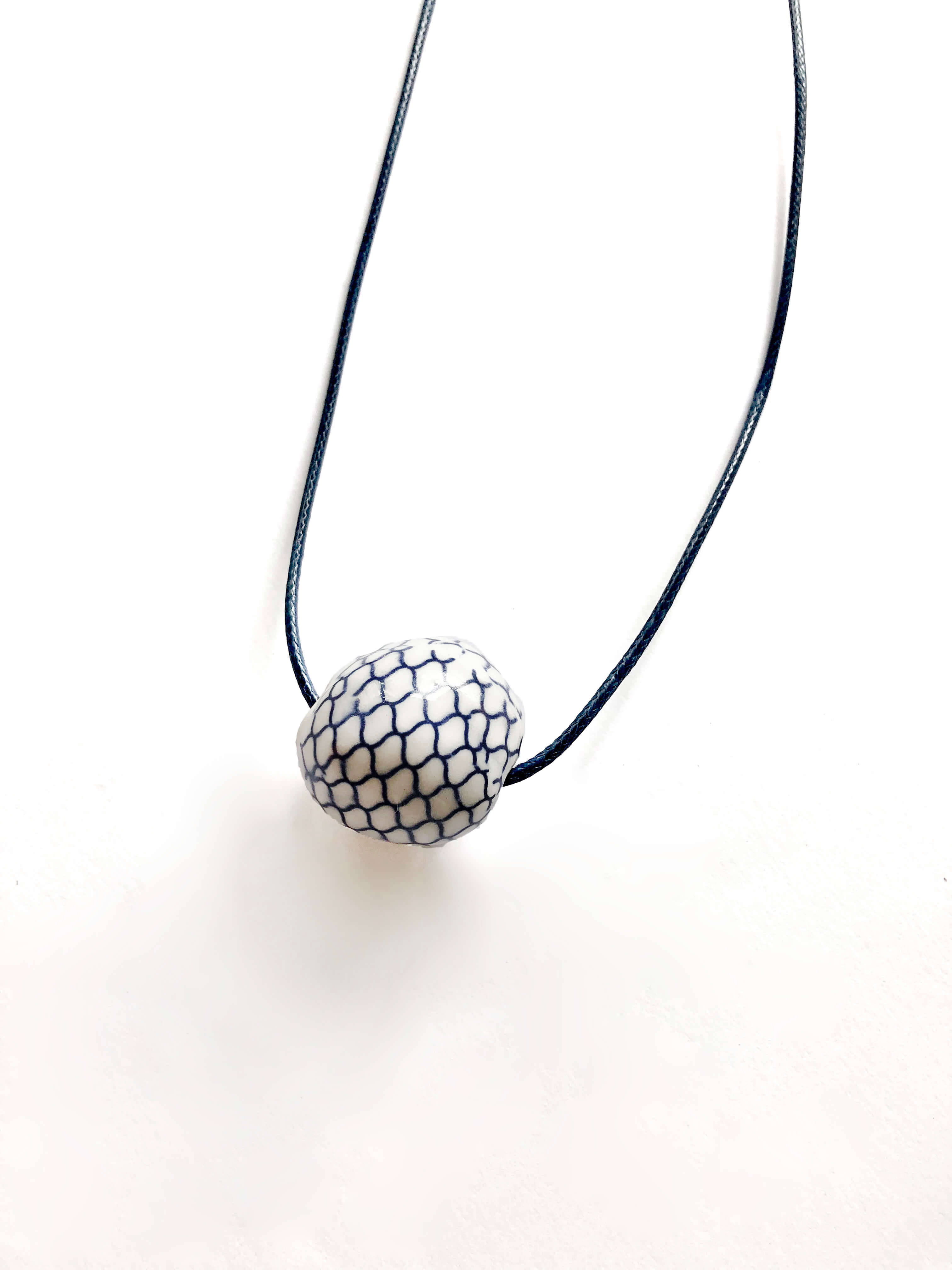 White ceramic necklace with blue fish-scale design
