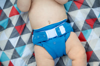 close up shot of a baby lying on a red and blue triangle shaped blanket wearing a blue grovia one cloth diaper kansas city baby co
