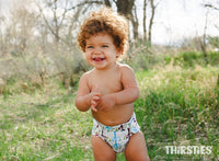toddler boy with brown hair standing outside with lots of greenery wearing a thirsties tree print cloth diaper kansas city baby co