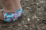 close up shot of baby wearing blue floral print smartbottoms diaper sitting on mulch kansas city baby co