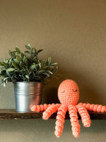 hand knit crochet octopus toy sitting on a wooden shelf with green plant june moon knits kansas city baby co