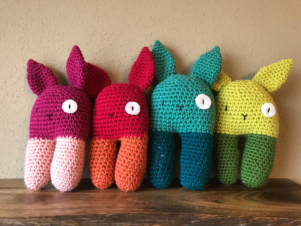 four multicolored crochet bunny rattles