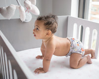 brown haired baby boy crawling in a white and gray crib wearing a fox print cloth diaper applecheeks kansas city baby co