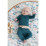 newborn baby boy in blue outfit lying on a blue and coral colored play mat grounded co kansas city baby co