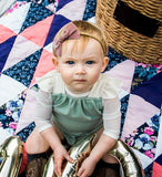 blonde haired toddler sitting on picnic blanket wearing soft pink addilyn rae handmade baby bow kansas city baby co