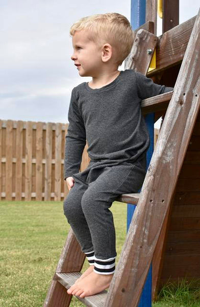 blonde toddler boy sitting on a ladder wearing charcoal colored romper kansas city baby co