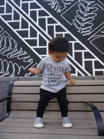 black haired toddler standing on a bench wearing black legging pants and a gray tshirt