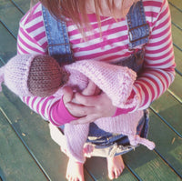 brown haired toddler girl in pink striped shirt and overalls holding a handknit crochet pink lovey doll kansas city baby co