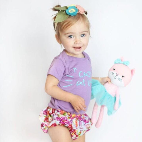 toddler girl with purple shirt and floral bottoms holding a pink cat stuffed toy kansas city baby co