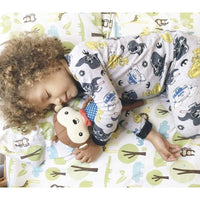 toddler boy with curly brown hair sleeping on a tree patterned sheet holding a hudson and heart monkey stuffed toy kansas city baby co