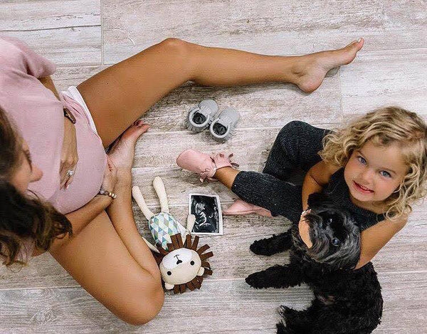 blonde haired toddler sitting on the ground with his mother playing with several toys hudson and heart lion stuffed animal kansas city baby co