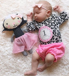 newborn baby sleeping on a soft white blanket wearing a leopard print onesie next to a hudson and heart lamb stuffed animal kansas city baby co
