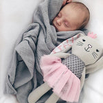 newborn baby swaddled in gray blanket snuggling a stuffed bunny wearing a pink tutu with a pink crown