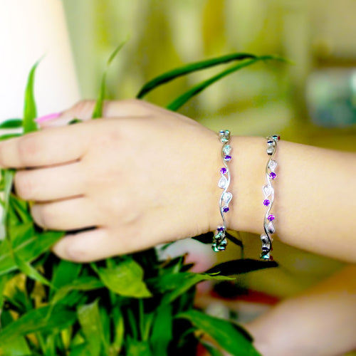 The handmade 92.5 silver bangle has silver curved lines and purple stone work with motifs. Ideal for indian look.