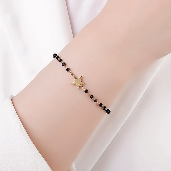 Woman wearing a black and gold beaded star bracelet