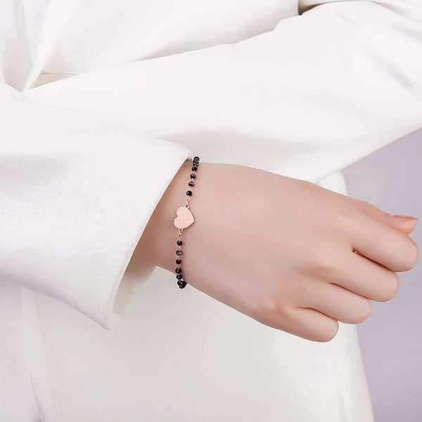 Woman wearing a black and rose gold beaded heart bracelet